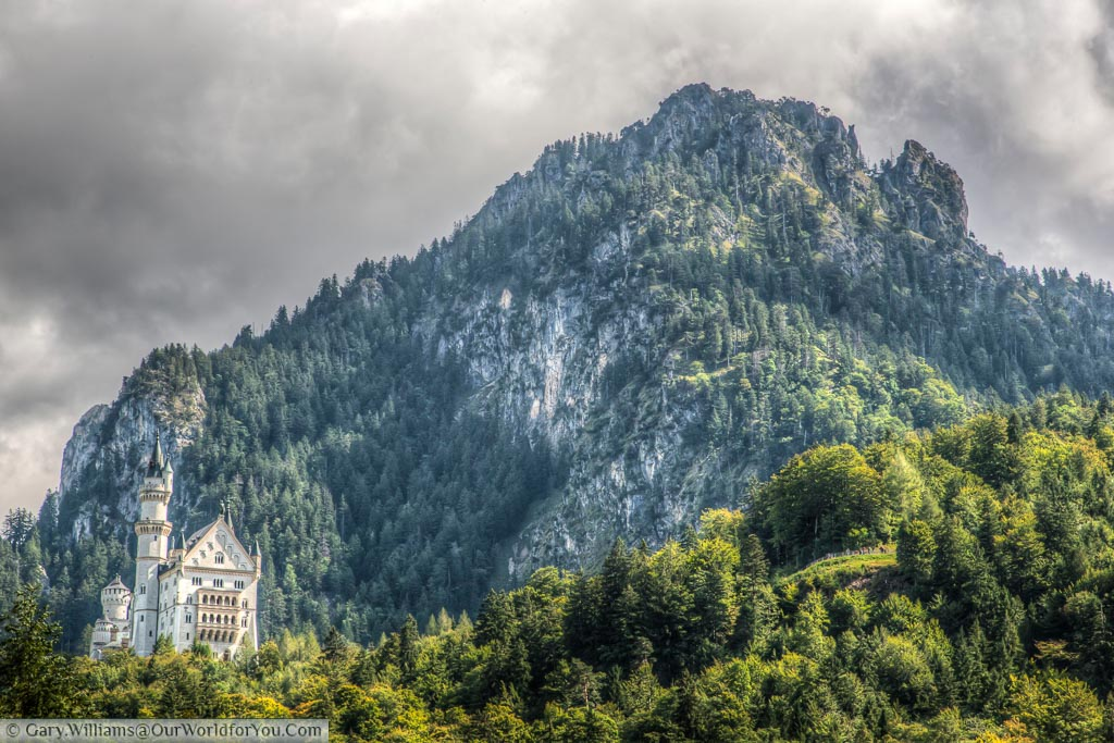 The magnificent Schloss Neuschwanstein set in deep Bavaria, dwarfed by the mountains behind it.