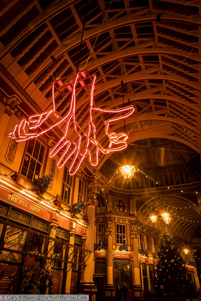 Inside Leadenhall Market at Christmas, looking towards the ceiling of this historic covered market within the City of London.  Hanging from the ceiling is an red neon light art installation of 3 hands reaching out, and at the Centre of the market is the Christmas tree.