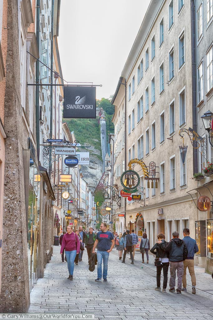 Walking along shopping street in central Salzburg, Each shop displays its own shop sign from an wrought iron sign holder.