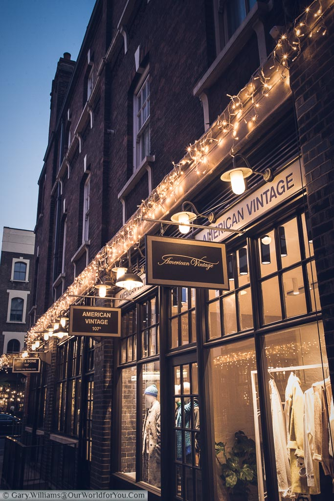 The American Vintage store at Spitalfields market at dusk.  The store has some decorative festive lights complementing the golden tones of the image.