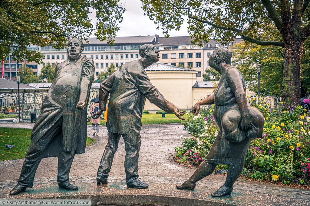 3 brass statues that make up part of the 'Circle of Money fountain in Aachen , Germany.  The first figure is the banker taking money with one hand and transferring it out round his back with another, the second figure is taking that money in one hand and passing on to his wife with his other hand.