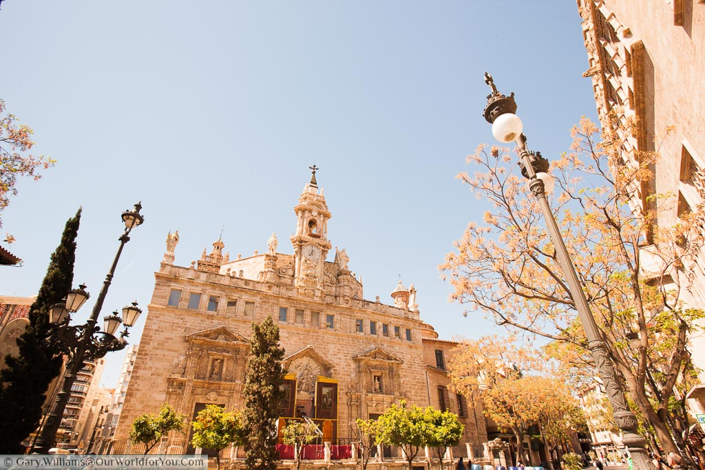 A beautifully ornate church in central Valencia distinguished with a triangular Bell tower, topped with statues of Saints on a golden spring day.