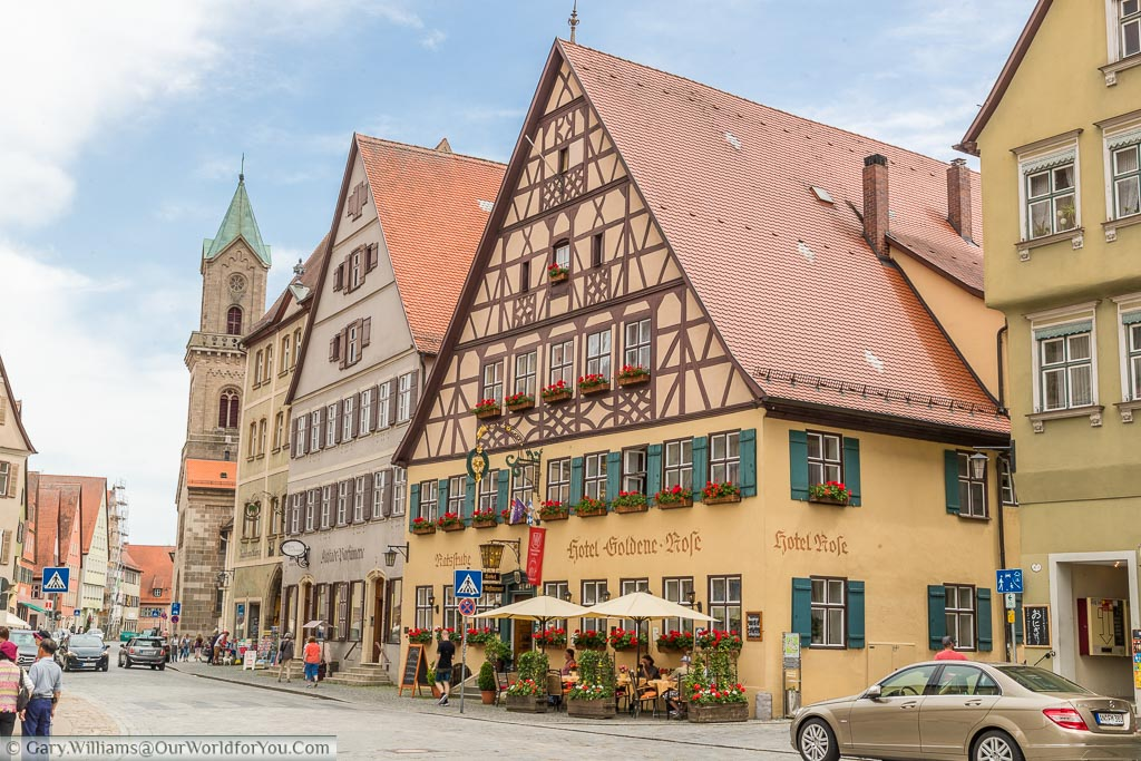 A street scene focused on the fabulous half-timbered Goldene Rose Hotel with window boxes full of red flowers with tables and chairs outside.