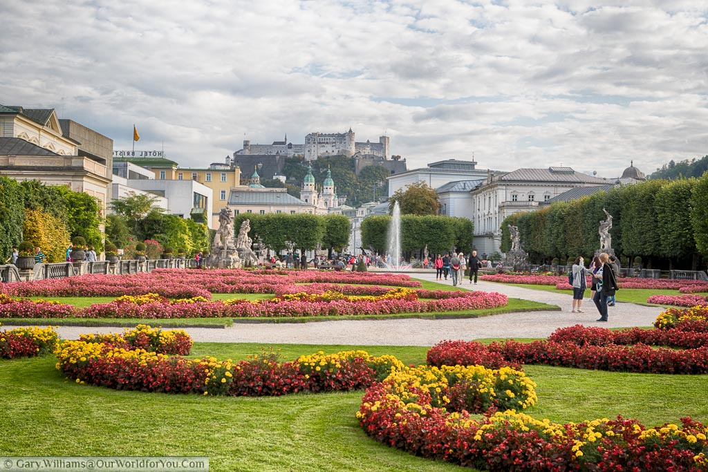 The Mirabell Palace Gardens in Salzburg with brightly coloured flower beds and fountain.  In the distance, high on the hill, you can see the city's Castle.