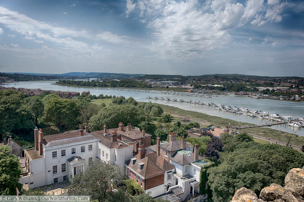 A view over the River Medway from Rochester Castle with scores of boats moored on the banks of the river. In the foreground is a large period mansion.