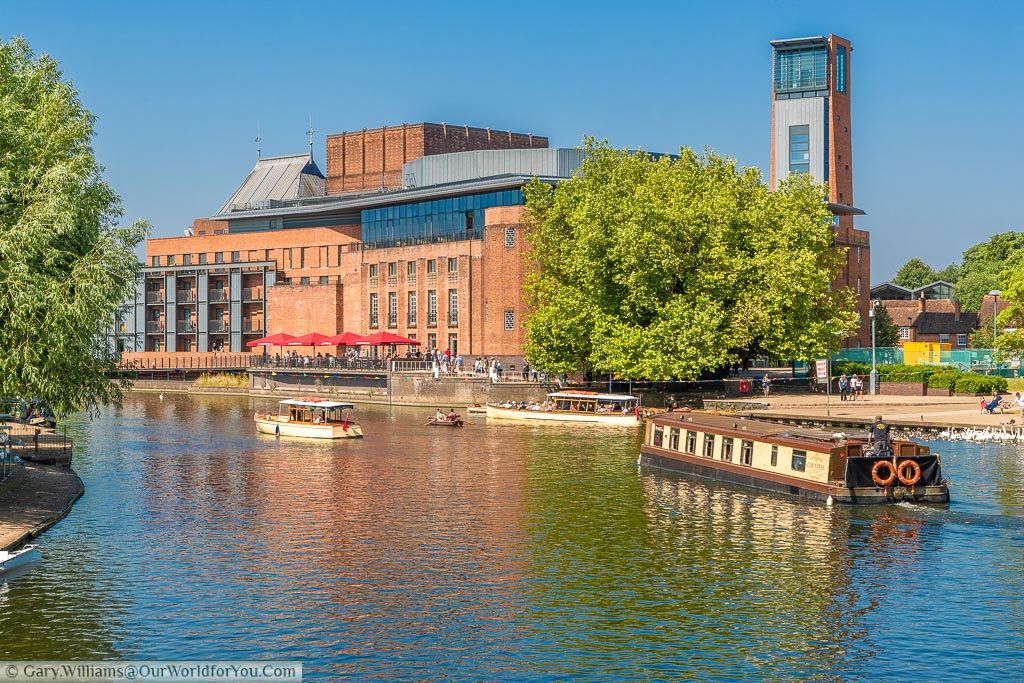 A wide-beam cnalboat navigating on the River Avon between other boats in front of the Royal Shakespeare Theatre on a beautiful sunny summers day.