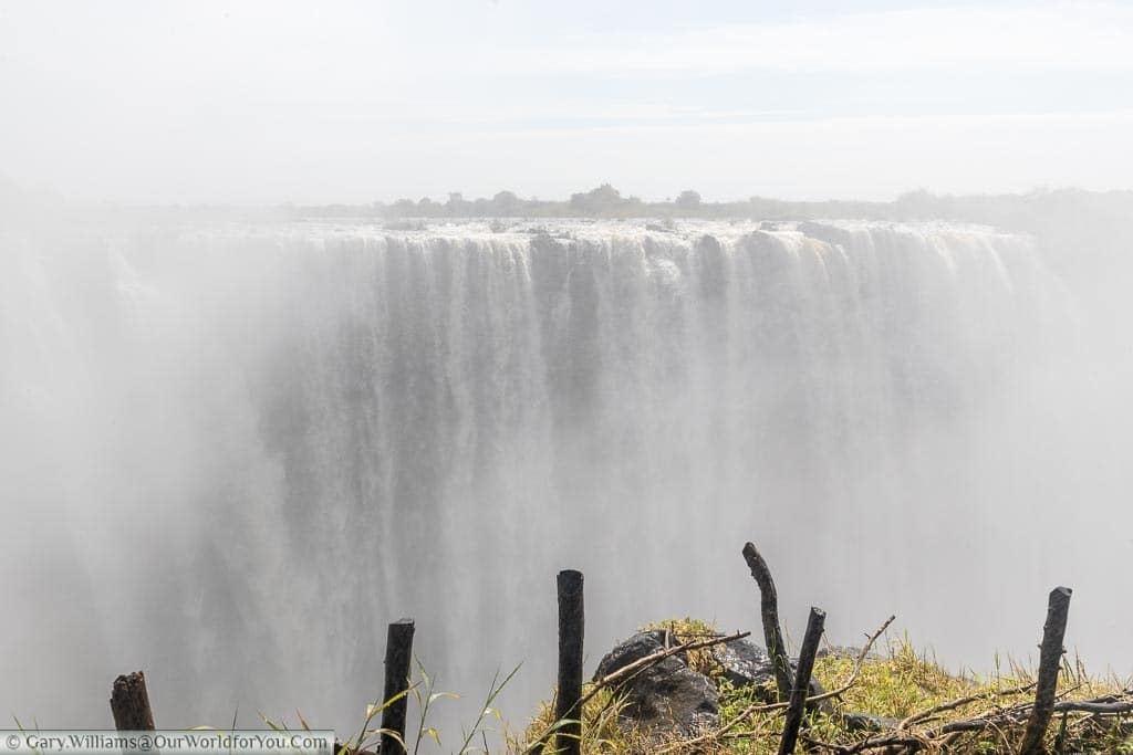 Standing at a viewpoint overlooking the main section of Victoria Falls. At high water season the amount of water cascading over the falls creates a heavy mist that hangs in the air.