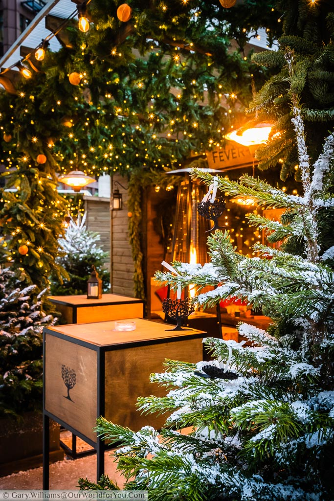 A portrait view of a secluded log cabin the Fever Tree stall at Broadgate's Winter Forest. The scene is edged with a Christmas trees and decorative fairy lights.