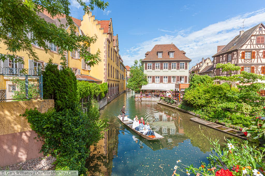 A family group enjoying a boat trip on the canals around Colmar in the Alsace region of France on a bright sunny summers day