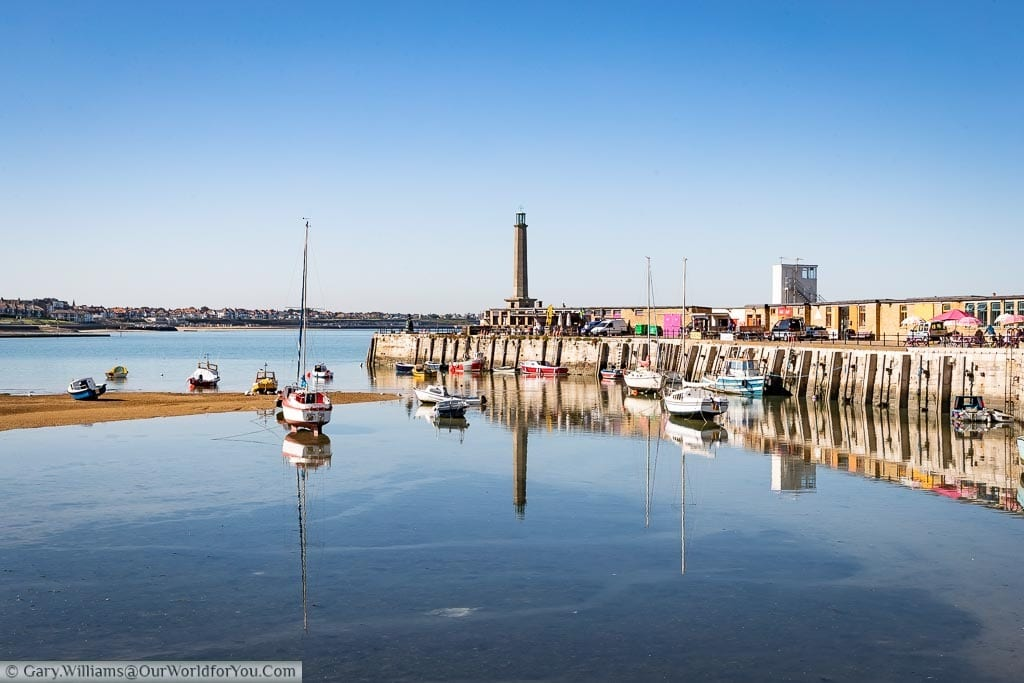 The Harbour at Margate on a bright day at low tide. Some boats are stranded on the sand banks and others partially floated. You can see the Harbour arm leading to the lighthouse at the tip of the Harbour's edge.