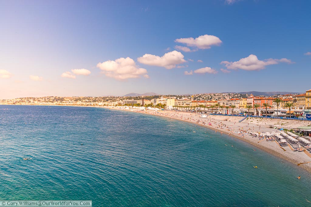 Beautiful blue waters leading up to the beach of Nice in southern France with holiday makers making the last of the autumn sunshine.