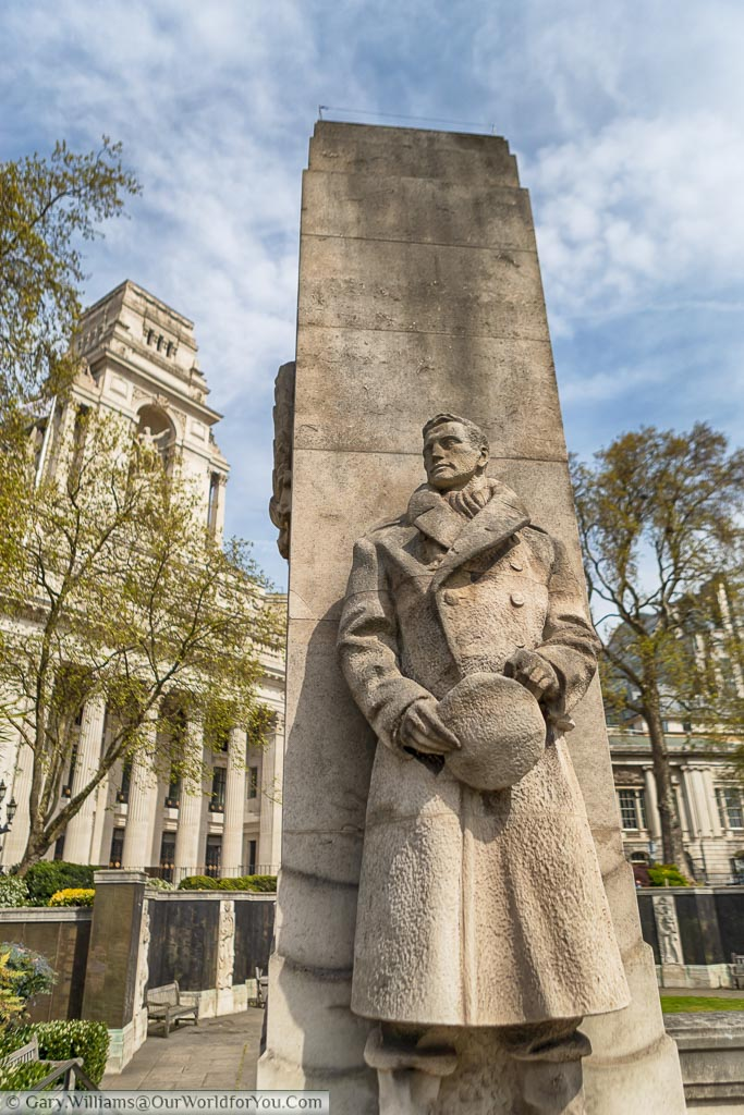 A sandstone statue of a naval officer, wrapped up warmly against harsh conditions, looking into the distance. In the background is Trinity house, a neo-classical designed piece of architecture on the edge of Tower Hill Memorial Gardens