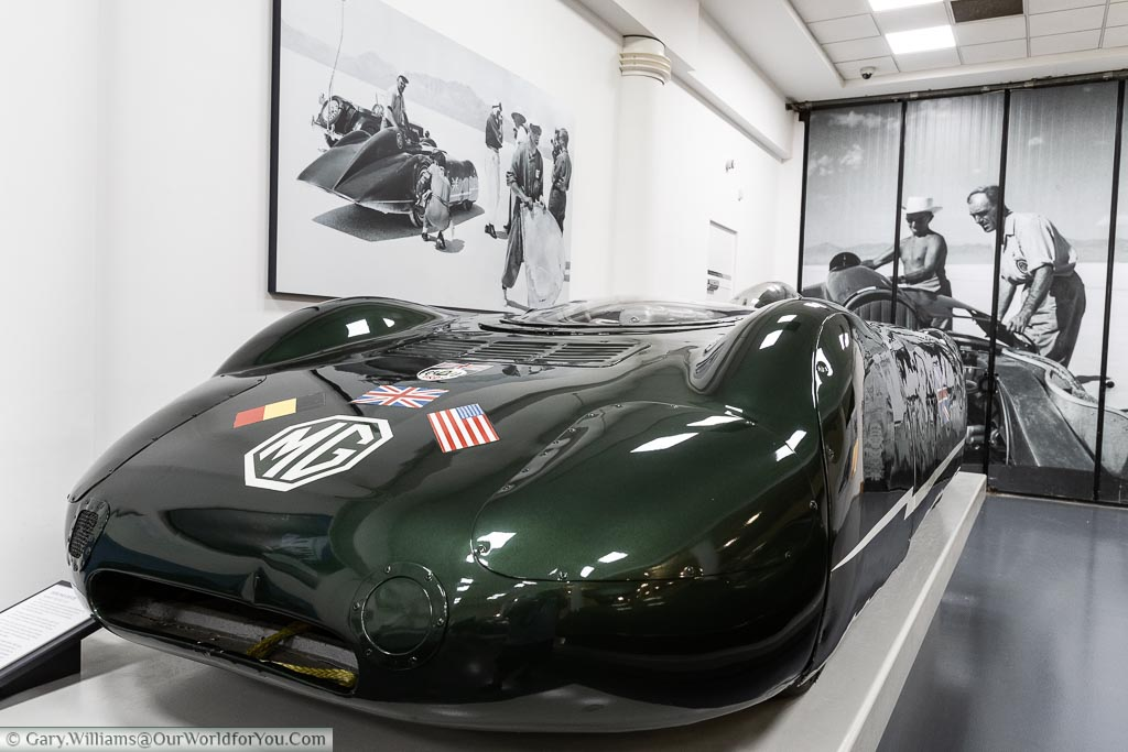 A streamlined car with an MG badge in a metallic British racing green, designed to tackle the Land Speed record, on display in British motor museum.