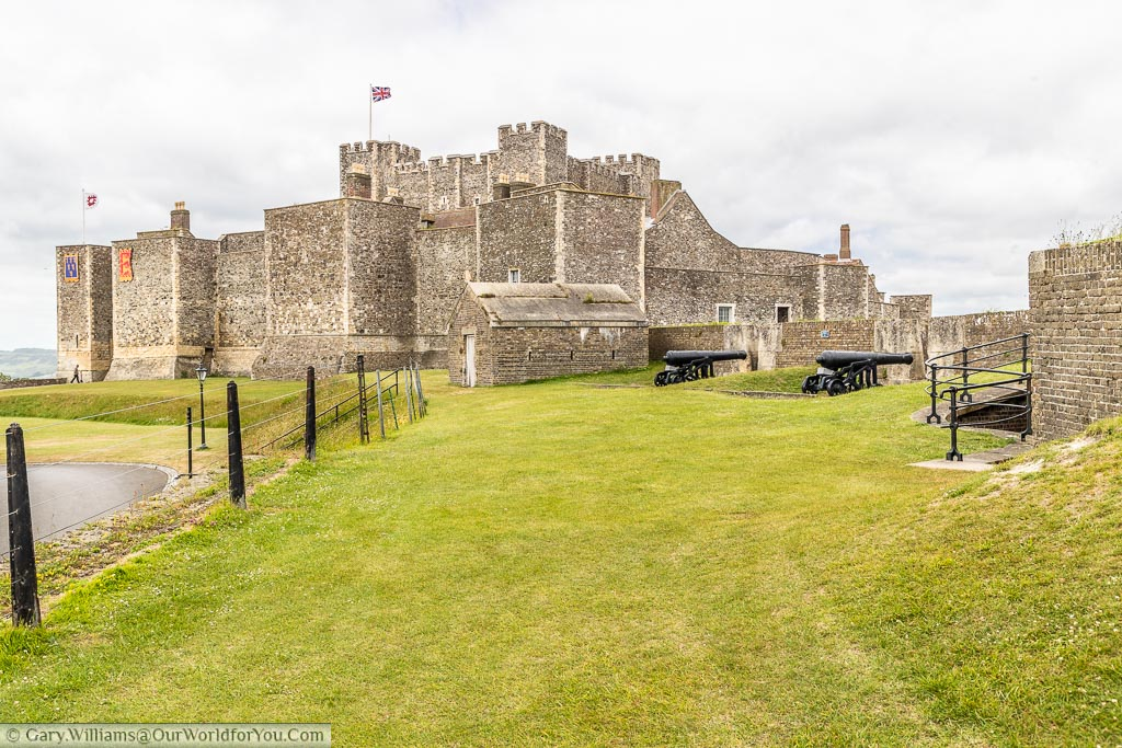 A view of Dover Castle from the grass banks that surround it. There are some cast iron Napoleonic cannons set defensive positions in the foreground.