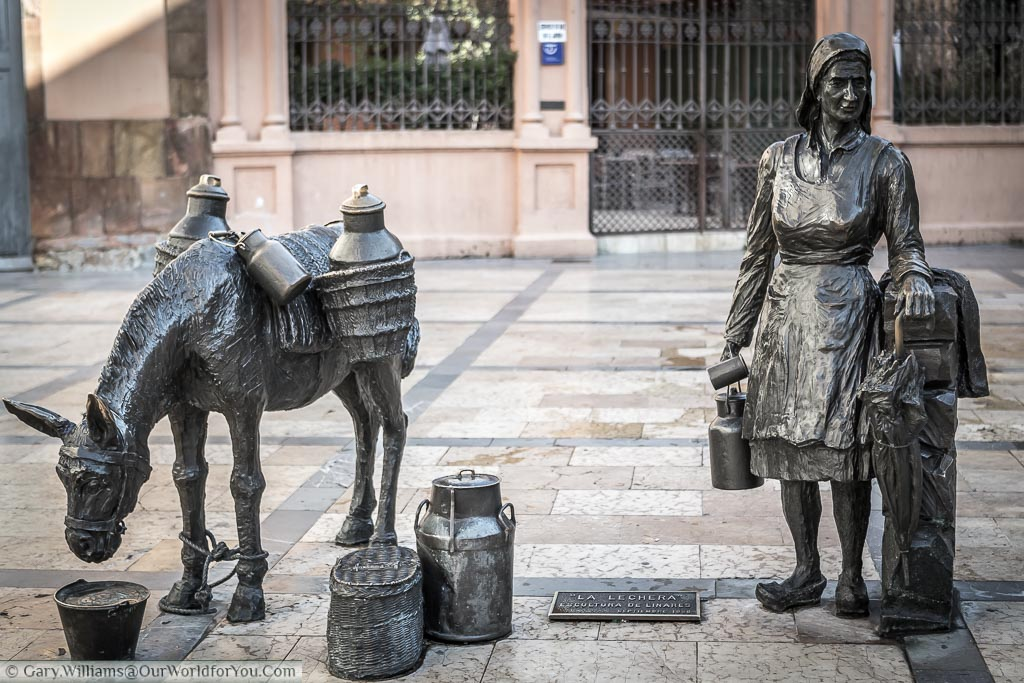 A brass statue of a milkmaid, along with her donkey, on the way to market in a square in Oviedo, Spain