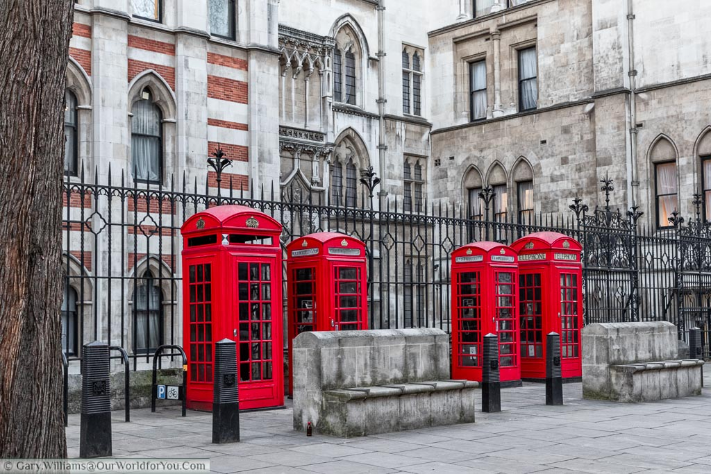 Bright red phone boxes; two large, two regular sized, in front of the Inns of Court in the City of London