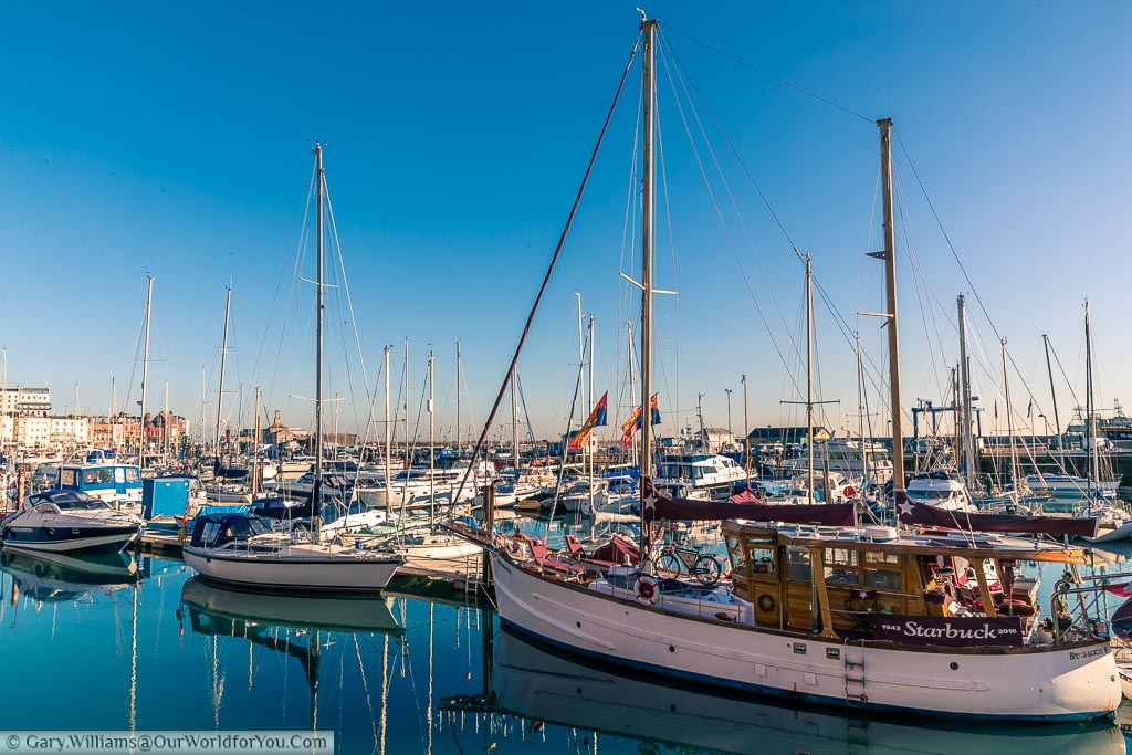 Small sailing boats in Ramsgate's Marina resting on perfectly still water under a bright blue sky.