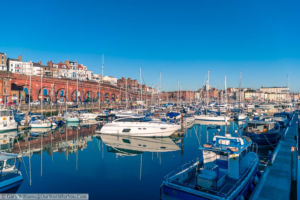 View from one corner of Ramsgate's Marina across the selection of different boats that take refuge here. This is set against the backdrop of the red brick colonnade that leads down to the Harbour front