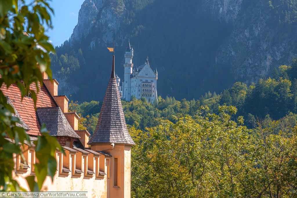 Looking past the orange ochre painted Hohenschwangau Castle to the white Schloss Neuschwanstein in the Bavarian hillside against a backdrop of mountains