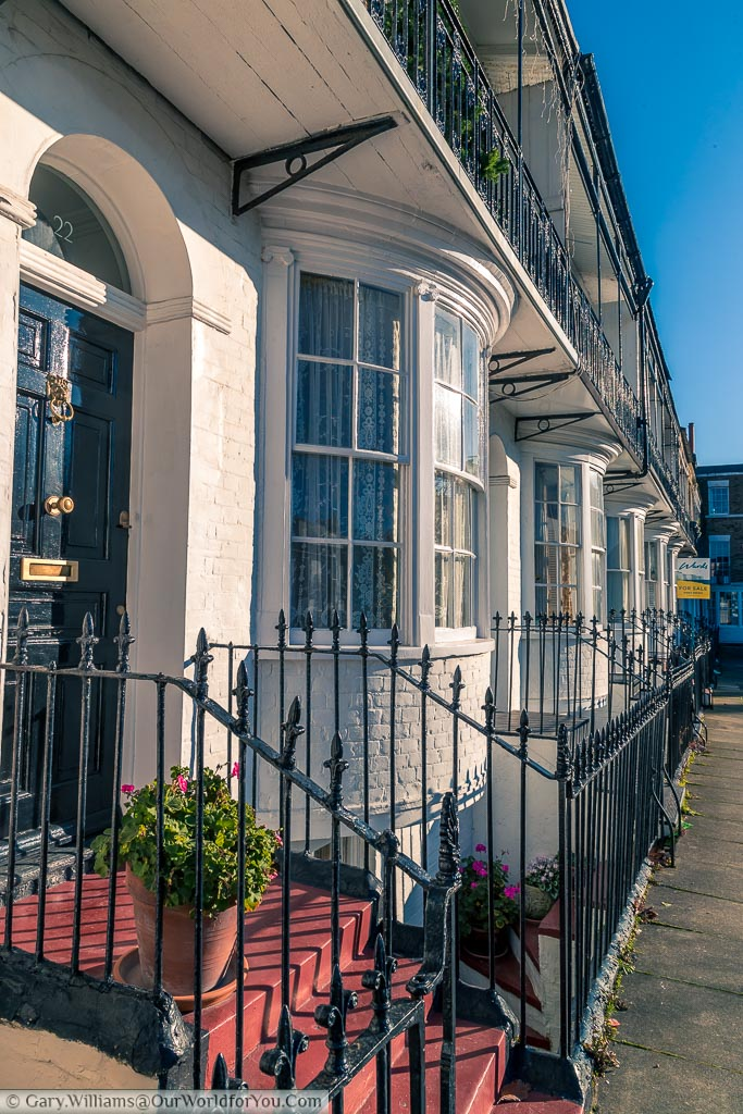 Black iron railings around the front of a series of elegant terraced homes in Spencer Square Ramsgate