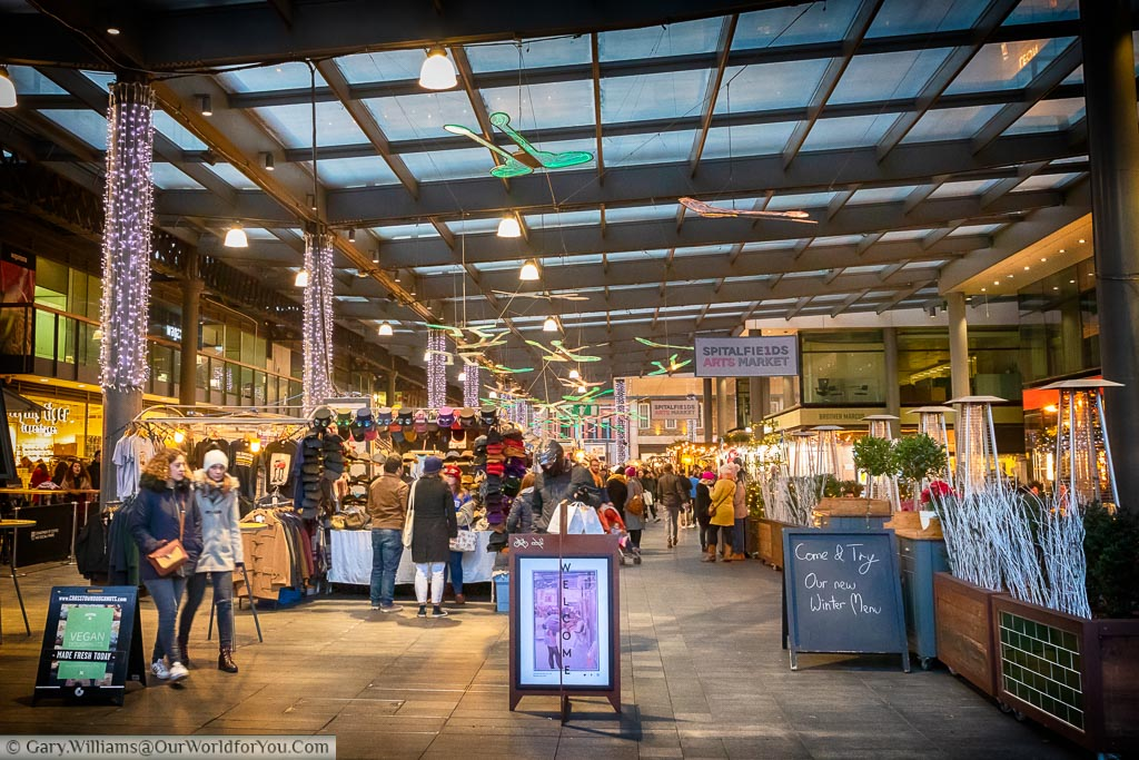 Looking into the bustling Spitalfields arts market that occupies an area where a market has been held for over 350 years.  The stalls are covered by glass roof these days things have become a little more artisan.