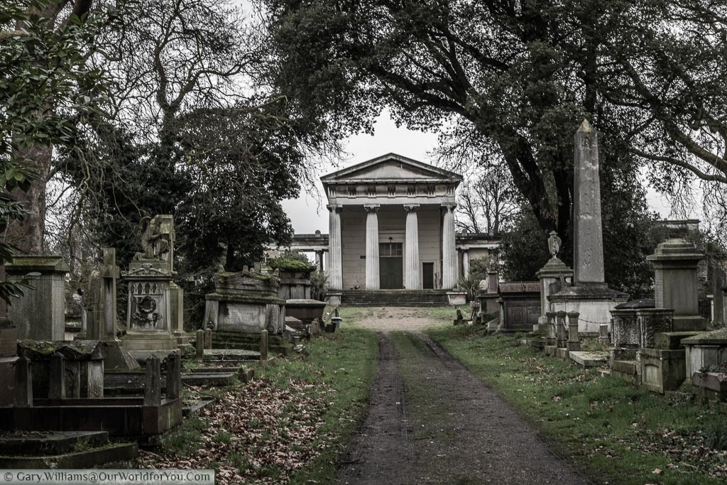 A path through Kensal Green Cemetery leading to the disused Anglican Chapel built in a neo-classical design with 4 Doric columns at the entrance. Either side of the way are tombs & gravestones.