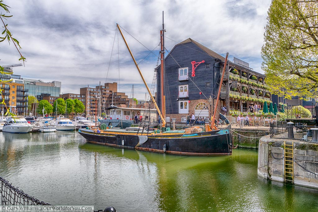 A sailing barge moored in front of the Dickens Inn at St Katharine docks