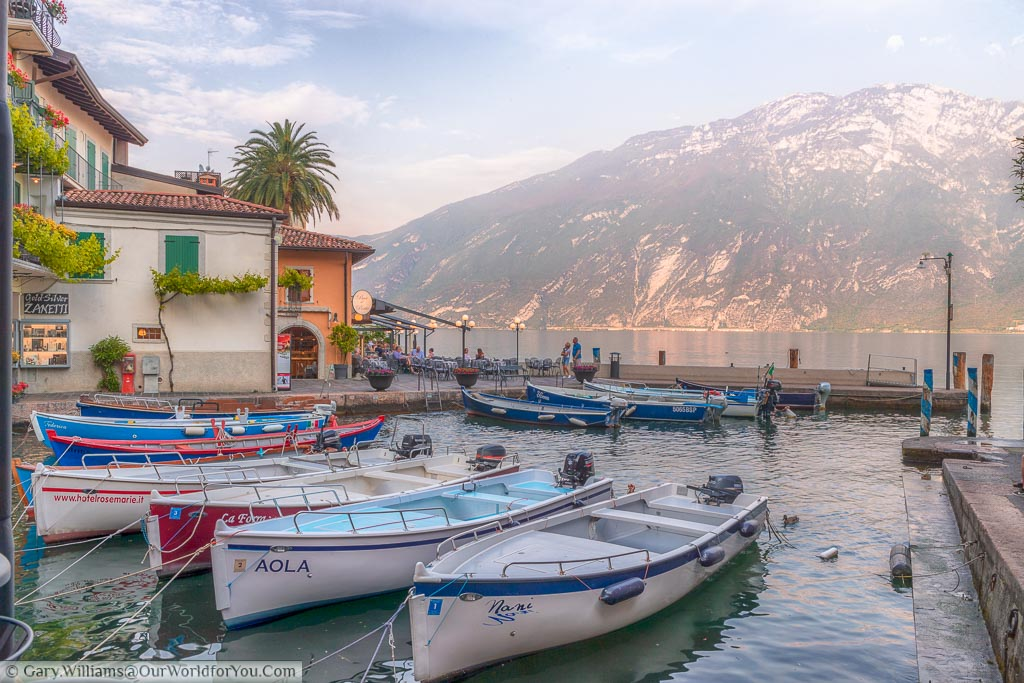 A dozen or so small boats in the picturesque little Harbour of Limone Sul Garda, on the edge of Lake Garda, with the backdrop of the mountains on the other side of the water.