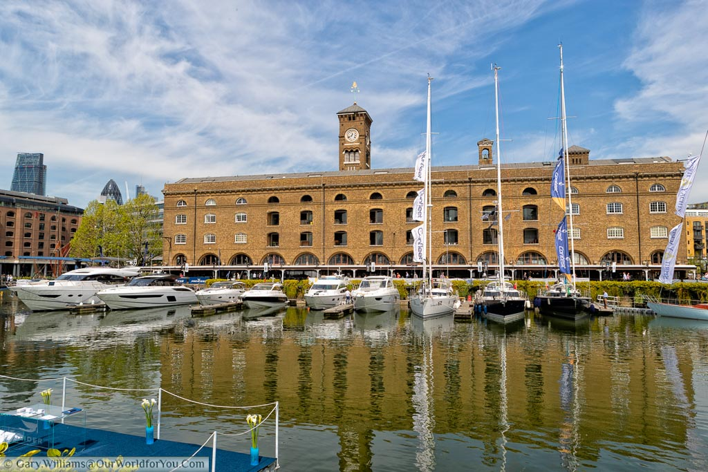 The Marina at St Katharine docks with a small selection of boats moored up in front of a brick built Victorian former warehouse with a clock tower