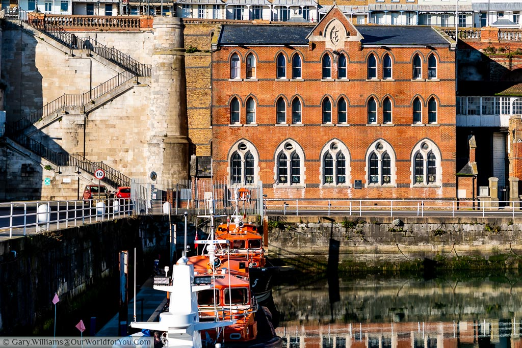 The red brick Sailors Church & Mission at the harbours edge. In the Harbour you can see pair of lifeboats moored up, ready for action