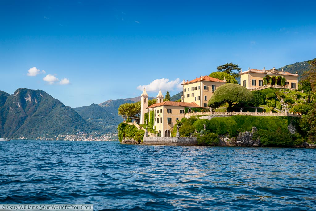 The palatial style Villa del Balbianello in sandy ones with terracotta tiled roofs against the backdrop of the deep blue water and blue skies of Lake Como