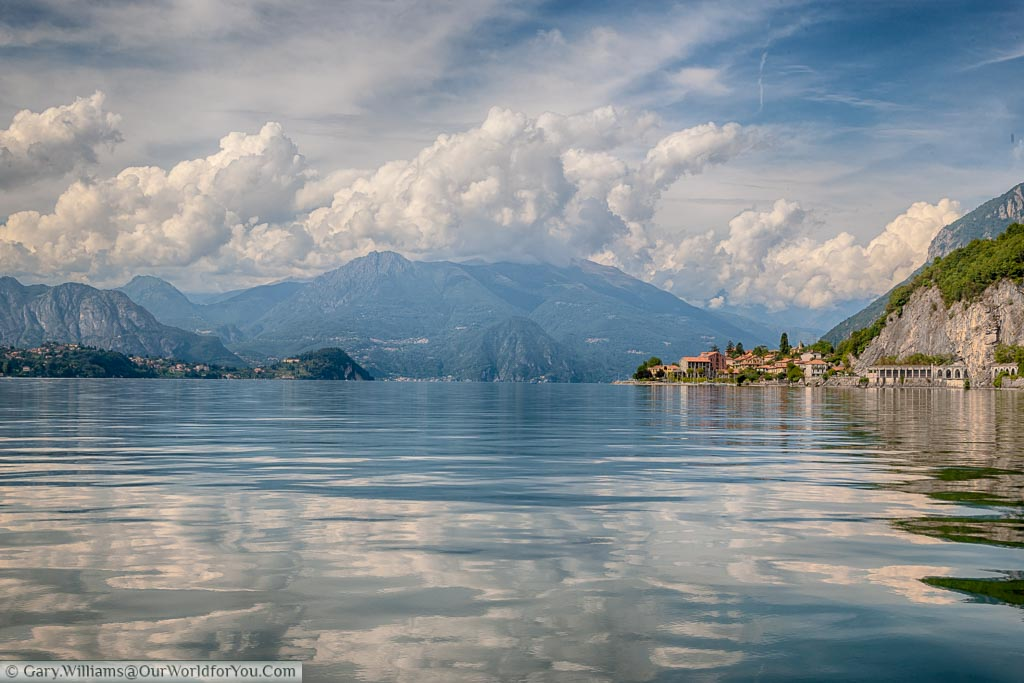 Shot taken from a boat on Lake Como where the light fluffy clouds in a blue sky are reflected in the water of the slightly rippling Lake. The vista is set against the mountainous backdrop and a small town on the right hand side edges into the Lake.