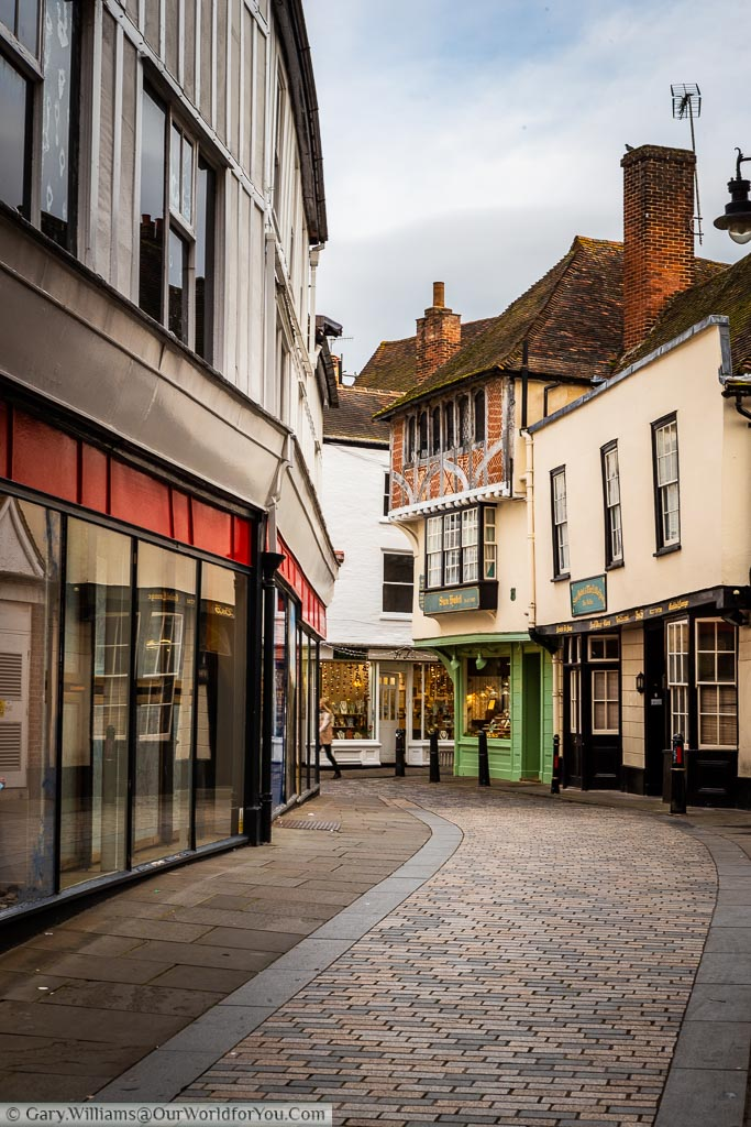 A view along a quiet cobbled lane in Canterbury towards a historic building that was once home to Charles Dickens and is now a jewellers.