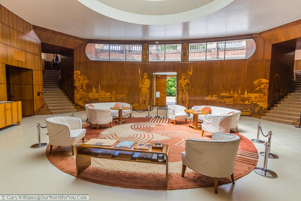 The opulent reception area of Eltham Palace in south east London with wood panels engraved with classical scenes. The whole area is an art deco masterpiece.
