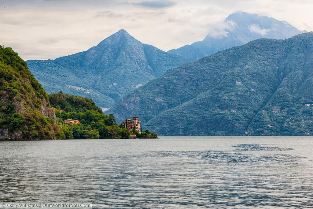 A shot taken from a boat on Lake Como of a villa at the edge of Lake Como with the green mountains acting as a backdrop against a slightly grey and cloudy sky.