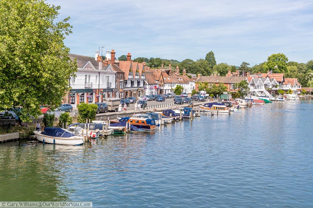 A number of small boats moored up at the Thames Riverside in Henley-on-Thames on a bright summers day.