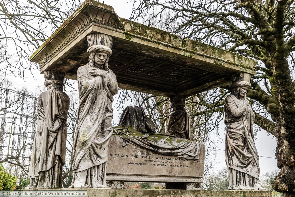 An ornate raised tomb to Major General Sir William Casement, K.C.B. The stone coffin chest is draped with a cloak and bicorn hat. The Canopy is supported by four Indian bearers, each wearing a turban and with his arms crossed.