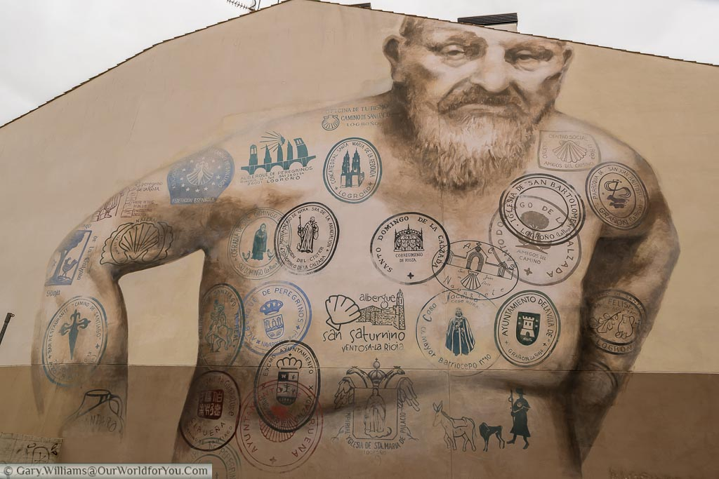 A mural on the end of a large building in Logroño of a barechested weary old traveller whose body is covered with 'tattoos' of the stamps of those who follow the Camino de Santiago. Logroño is one of the many stops on the way to Santiago de Compostela.