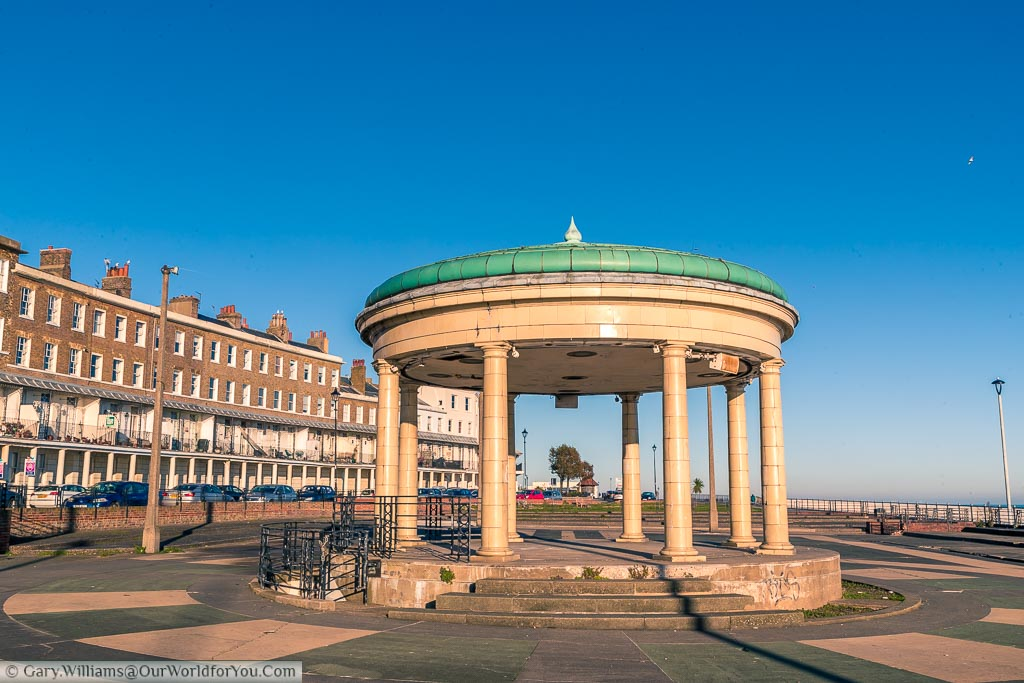 Ramsgate's bandstand in Wellington Crescent with the green glazed tiled roof above a cream tiled bandstand.