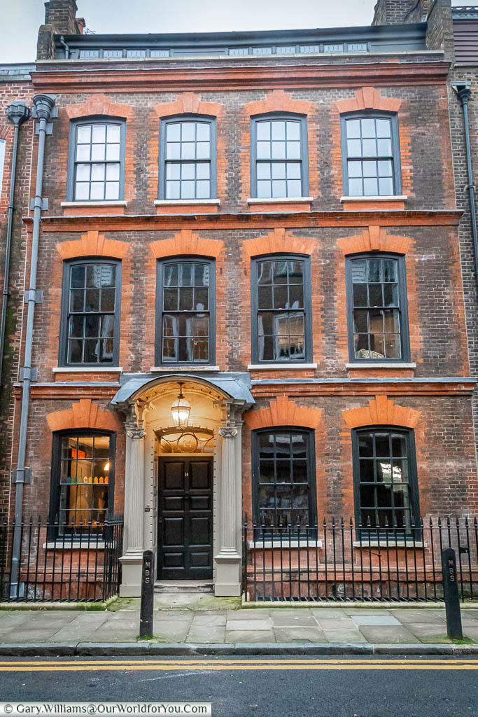 14 Fournier Street, leading away from Spitalfields is a 3 storey brick-built terraced building with a grand entrance lit by a hanging Georgian lantern.