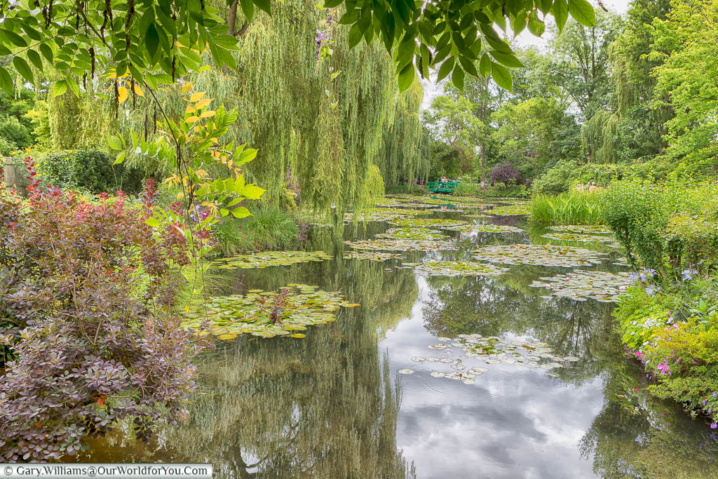 The view across the lily pond to a green footbridge in the distance in Claude Monet's gardens in Giverny, Normandy