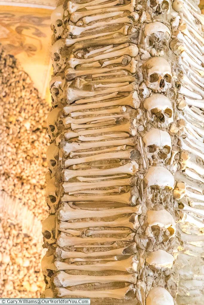 A close-up of skulls & bones that adorn one of the columns in the Chapel of Bones in Évora