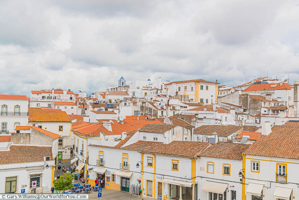 A rooftop view of the whitewashed building, trimmed in yellow, with their terracotta roofs, from the Igreja de São Francisco in Évora on a cloudy day.