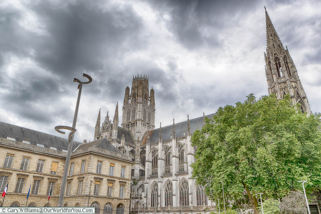 The gothic Abbey of Saint Oeun in Rouen under dark, brooding, skies.