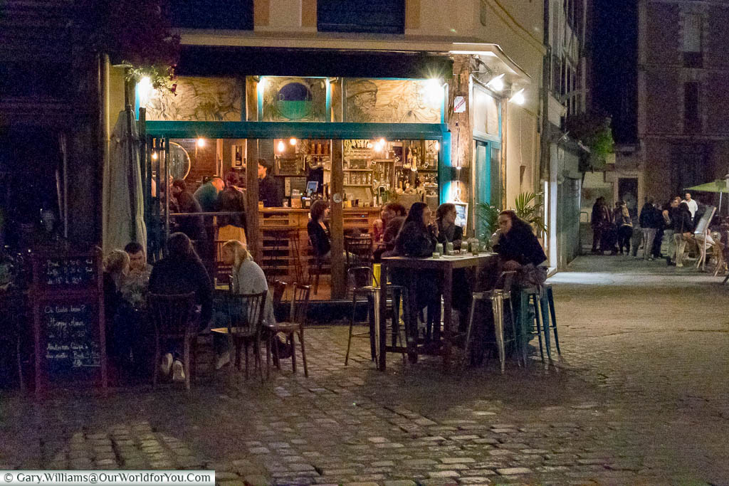 An evening scene of people sitting both inside and outside a cafe/bar in Rouen.