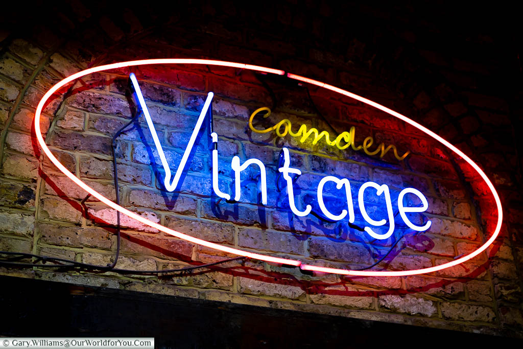 A neon sign for Camden Vintage mounted directly on the brickwork in  Camden Market.