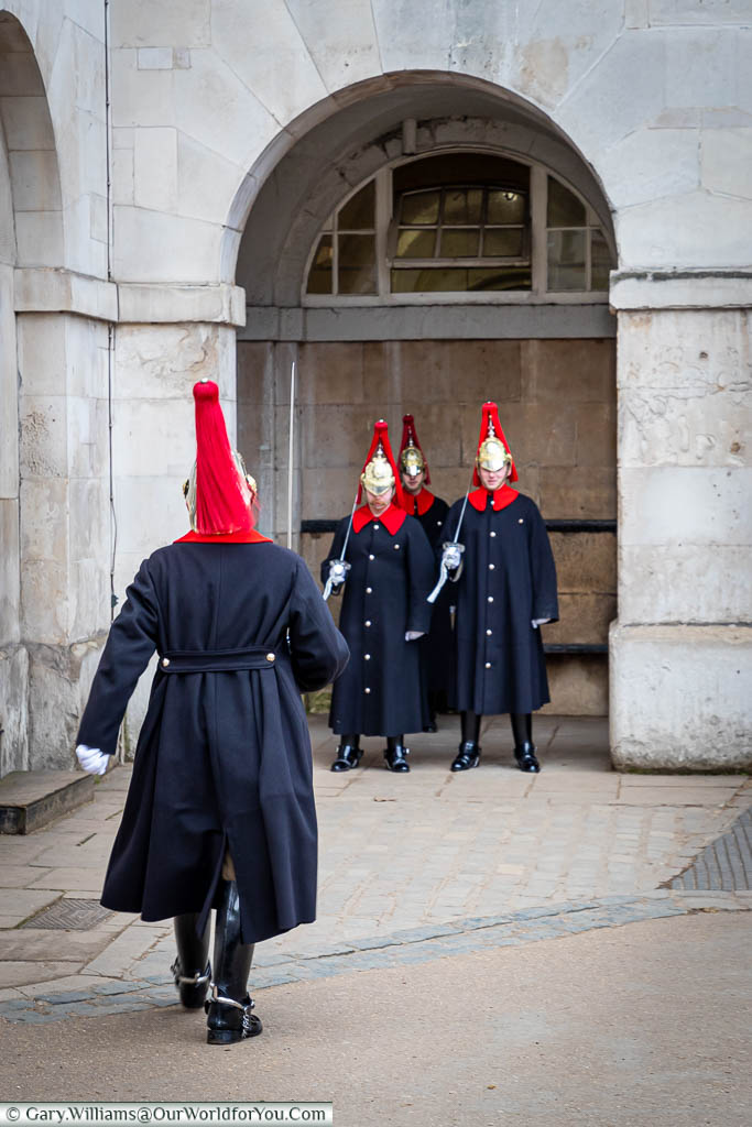 A single sentry from the Blues and Royals, in a uniform consisting of dark blue coats with vibrant red collars with red plumed helmets, marches towards three other sentries during the changing of the guard.