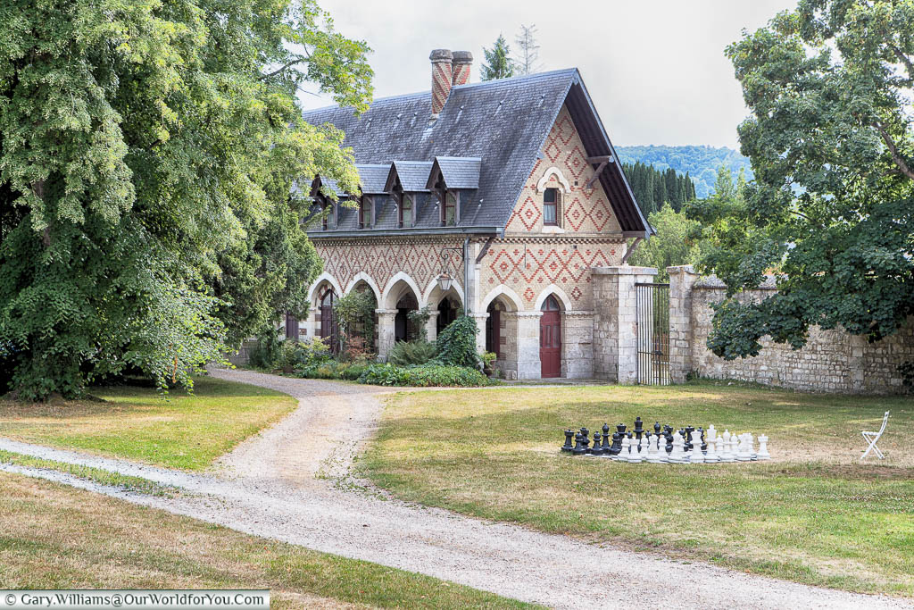 An outdoor chess set sits in the grounds of Jumieges Abbey in front of a restored building.