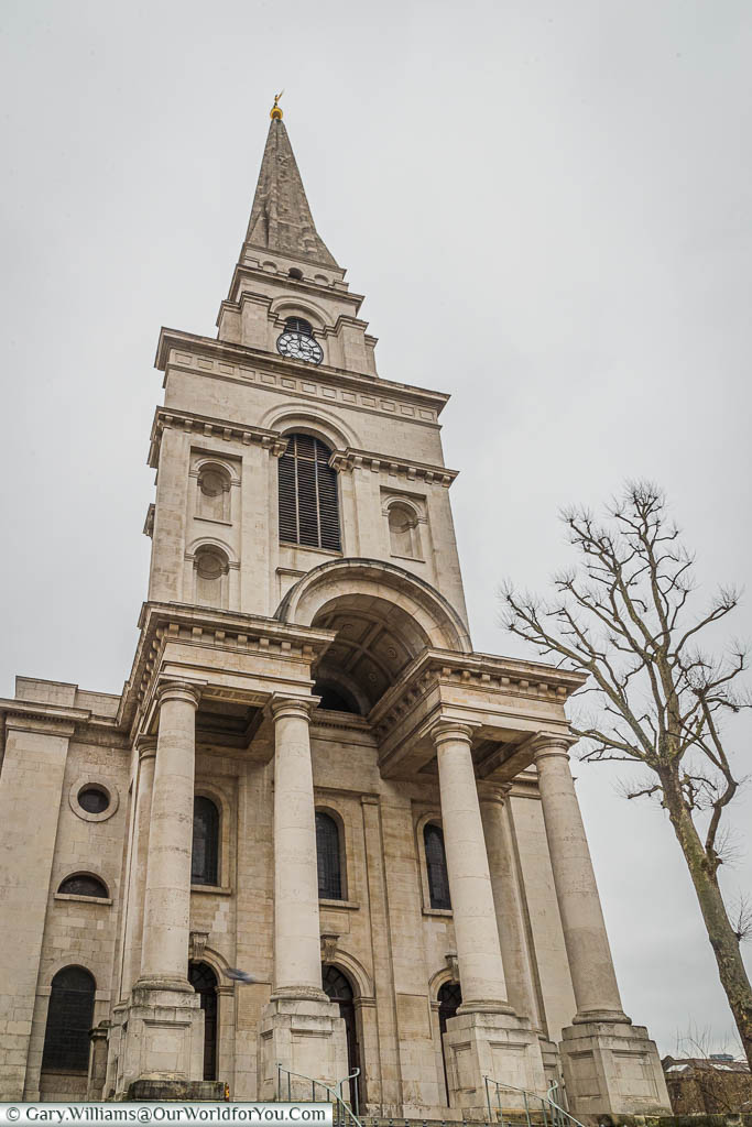 The impressive entrance and spire to Christ Church, Spitalfields.  A tall cream stone church, with 4 huge columns at the entrance leading up to a pointed bell-tower.