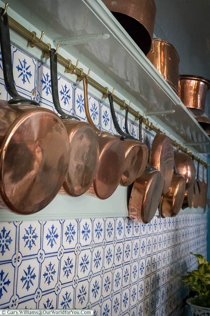 Copper pans and pots are hanging on the wall in the kitchen of Claude Monet's home.